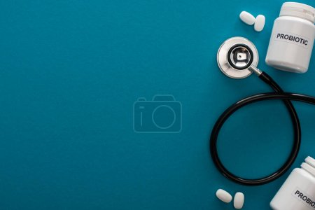 top view of containers with probiotic lettering, pills and stethoscope on blue background