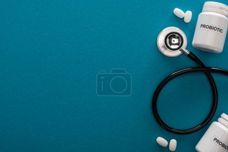Photo for Top view of containers with probiotic lettering, pills and stethoscope on blue background - Royalty Free Image