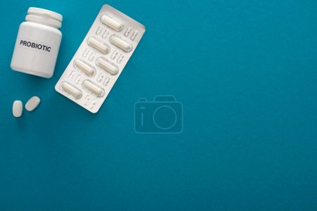 Photo for Top view of container with probiotic lettering, pills and blister pack on blue background - Royalty Free Image