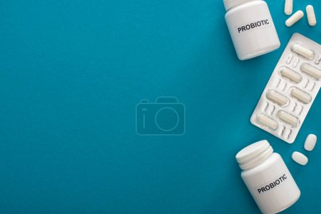Photo for Top view of containers with probiotic lettering, pills and blister pack on blue background - Royalty Free Image
