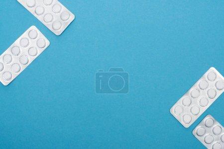 Photo pour Vue du dessus des pilules en plaquettes thermoformées sur fond bleu - image libre de droit