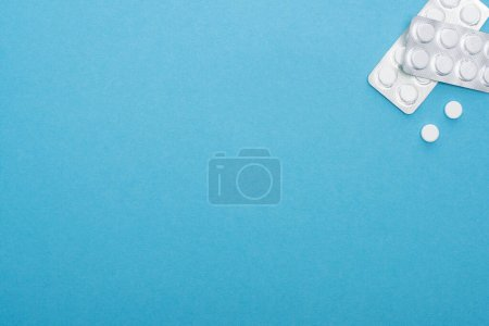 top view of pills in blister packs on blue background