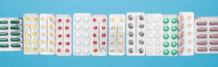Photo for Top view of colorful pills in blister packs on blue background, panoramic orientation - Royalty Free Image