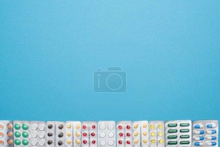 Photo pour Vue du dessus des pilules colorées en plaquettes thermoformées sur fond bleu avec espace de copie - image libre de droit