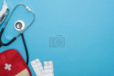 Photo pour Vue du dessus des pilules en plaquettes thermoformées, trousse de premiers soins, thermomètre auriculaire et stéthoscope sur fond bleu - image libre de droit