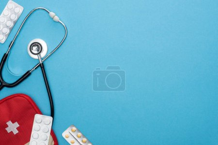 top view of pills in blister packs, first aid kit and stethoscope on blue background