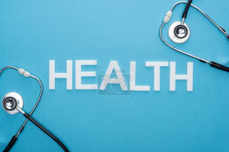Photo for Top view of health lettering and stethoscopes on blue background - Royalty Free Image