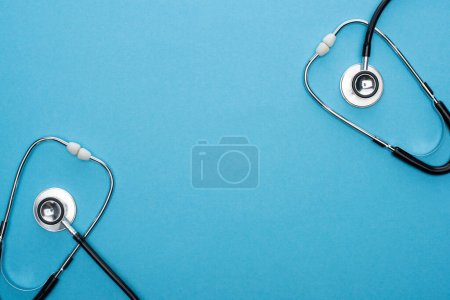 top view of stethoscopes on blue background