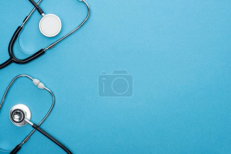 Photo for Top view of stethoscopes on blue background - Royalty Free Image