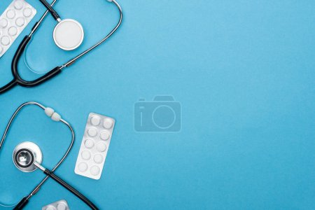 Photo for Top view of pills in blister packs and stethoscopes on blue background - Royalty Free Image