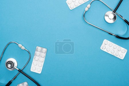 top view of pills in blister packs and stethoscopes on blue background
