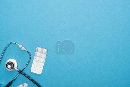 Photo pour Vue du dessus des pilules en plaquettes thermoformées et stéthoscope sur fond bleu - image libre de droit