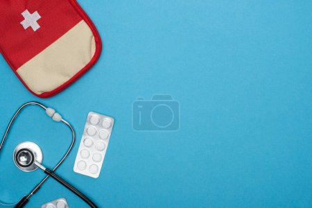 Photo for Top view of pills in blister pack, stethoscope, first aid kit on blue background - Royalty Free Image
