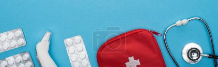 Photo for Top view of pills in blister packs, stethoscope, first aid kit and ear thermometer on blue background, horizontal image - Royalty Free Image