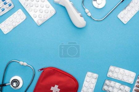Photo pour Vue du dessus des pilules en plaquettes thermoformées, stéthoscopes, trousse de premiers soins et thermomètre auriculaire sur fond bleu - image libre de droit