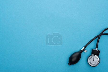 top view of sphygmomanometer on blue background
