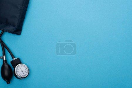 Photo pour Vue du dessus du sphygmomanomètre sur fond bleu - image libre de droit