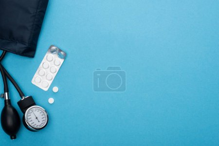 top view of pills in blister pack, sphygmomanometer on blue background