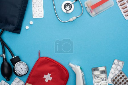 top view of ear thermometer, pills in blister packs, sphygmomanometer, first aid kit and stethoscope on blue background