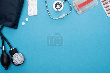 Photo pour Vue du dessus des pilules en plaquettes thermoformées, sphygmomanomètre et stéthoscope sur fond bleu - image libre de droit