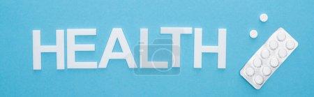 Photo pour Vue du dessus des pilules en blister et lettrage santé sur fond bleu, prise de vue panoramique - image libre de droit