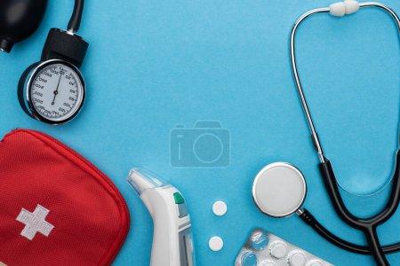 Photo pour Vue du dessus du sphygmomanomètre, pilules en plaquette thermoformée, stéthoscope, trousse de premiers soins et thermomètre auriculaire sur fond bleu - image libre de droit