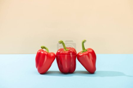 Photo for Fresh red bell peppers on blue surface isolated on beige - Royalty Free Image
