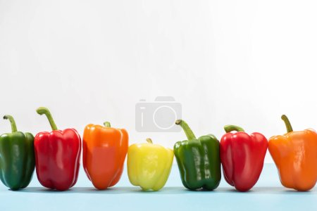 Photo for Fresh colorful bell peppers on blue surface on white background - Royalty Free Image