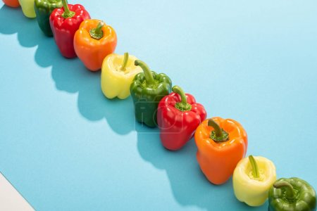 Photo for Fresh colorful bell peppers in row on blue surface - Royalty Free Image