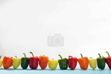 Photo for Fresh colorful bell peppers in row on blue surface on white background - Royalty Free Image