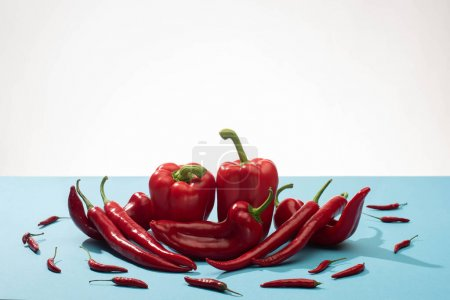 Photo for Fresh red bell peppers and chili on blue surface on white background - Royalty Free Image
