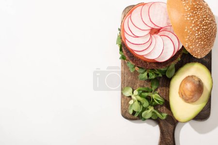 Photo for Top view of delicious vegan burger with radish, avocado and greens on wooden cutting board on white background - Royalty Free Image