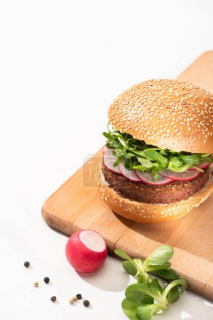 Photo for Delicious vegan burger with radish and arugula on wooden board with black pepper on white background - Royalty Free Image