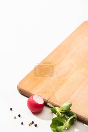 Photo for Delicious radish and greens with black pepper near wooden board on white background - Royalty Free Image