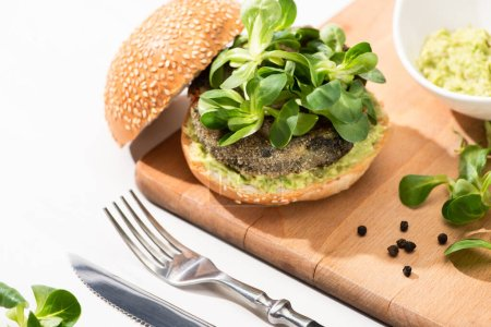 Photo for Delicious green vegan burger with microgreens and mashed avocado on wooden boar with black pepper near fork and knife on white background - Royalty Free Image
