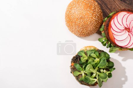 Photo for Top view of vegan burgers with microgreens, radish on cutting board on white background - Royalty Free Image