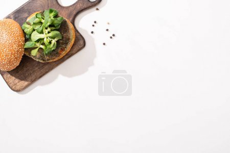 Photo for Top view of vegan burger with microgreens on wooden board on white background - Royalty Free Image