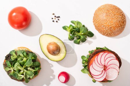 Photo for Top view of vegan burgers with ingredients on white background - Royalty Free Image