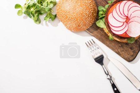 Photo pour Vue de dessus du hamburger végétalien avec microgreens, radis sur planche à découper en bois près des couverts sur fond blanc - image libre de droit