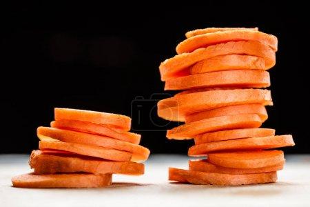 Photo pour Vue de près de tranches de carottes fraîches et mûres isolées sur noir - image libre de droit