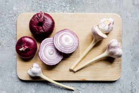 Photo for Top view of onion and garlic on wooden cutting board on grey concrete surface - Royalty Free Image