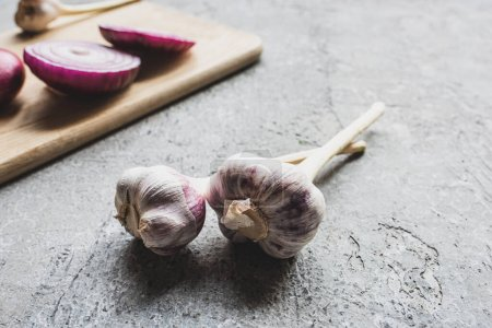 Photo for Selective focus of garlic near onion on wooden cutting board on grey concrete surface - Royalty Free Image