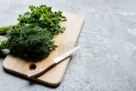 Photo for Green parsley and dill on cutting board with knife on grey concrete surface - Royalty Free Image