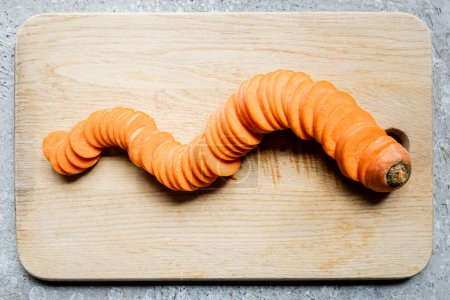 Photo for Top view of fresh ripe carrot slices on wooden cutting board on concrete surface - Royalty Free Image