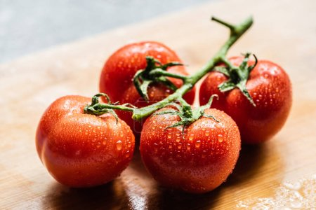 Photo for Fresh ripe red tomatoes on branch with water drops on wooden board - Royalty Free Image