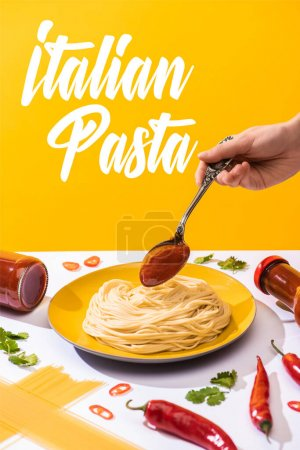 Cropped view of woman adding ketchup to spaghetti on white surface isolated on yellow, Italian pasta illustration