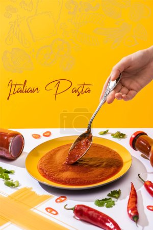 Photo for Cropped view of woman holding spoon with ketchup with spaghetti and chili peppers on white surface isolated on yellow, Italian pasta illustration - Royalty Free Image
