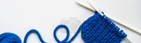 Photo for Top view of blue wool yarn and knitting needles on white background, panoramic orientation - Royalty Free Image