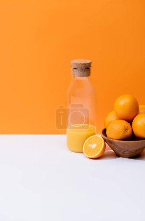Photo for Fresh orange juice in glass bottle near oranges in bowl on white surface isolated on orange - Royalty Free Image
