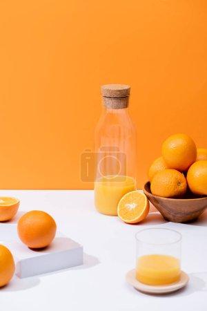 Photo for Fresh orange juice in glass and bottle near oranges in bowl on white surface isolated on orange - Royalty Free Image